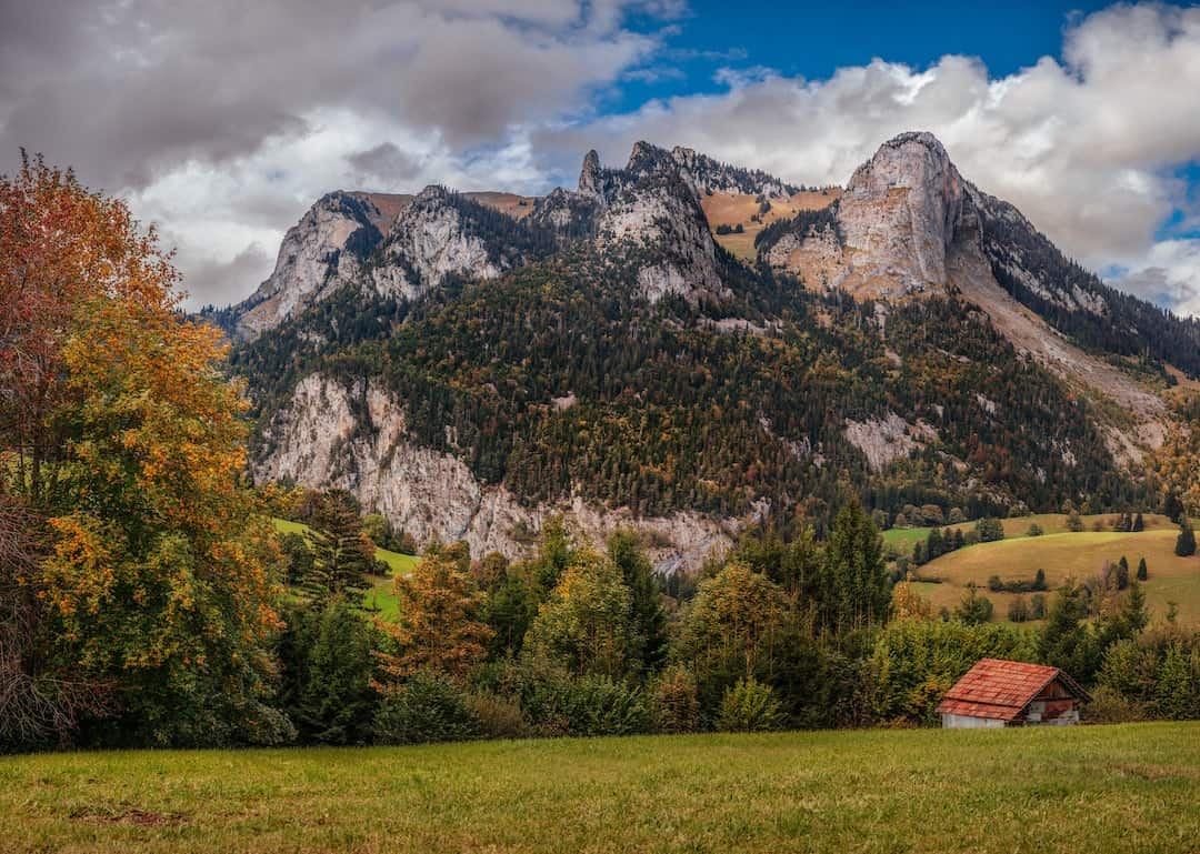 A small hut in front of mountains and trees in autumn