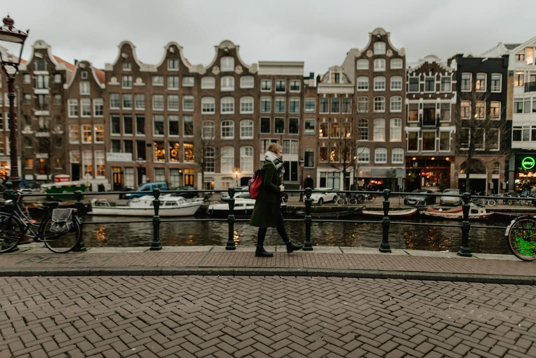 A woman walking beside a canal in Amsterdam