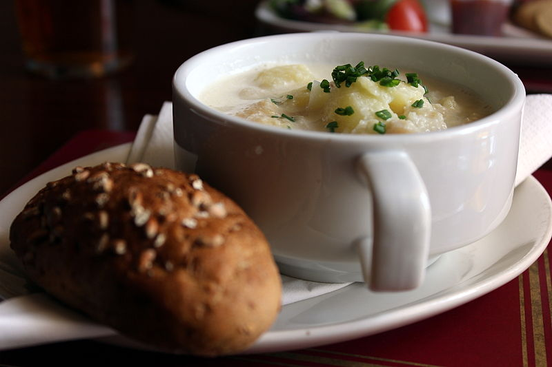 A bowl of cullen skink and a bread roll at a restaurant in Scotland