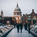people walking on a bridge with a view of st. paul's cathedral in the background