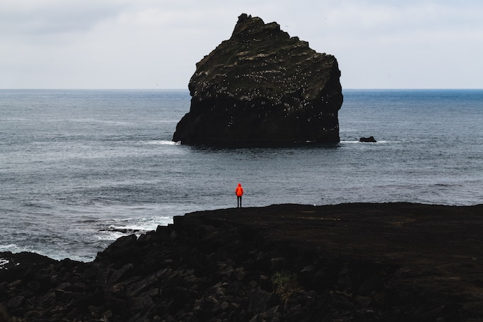 a person standing on a black sand beach in Iceland