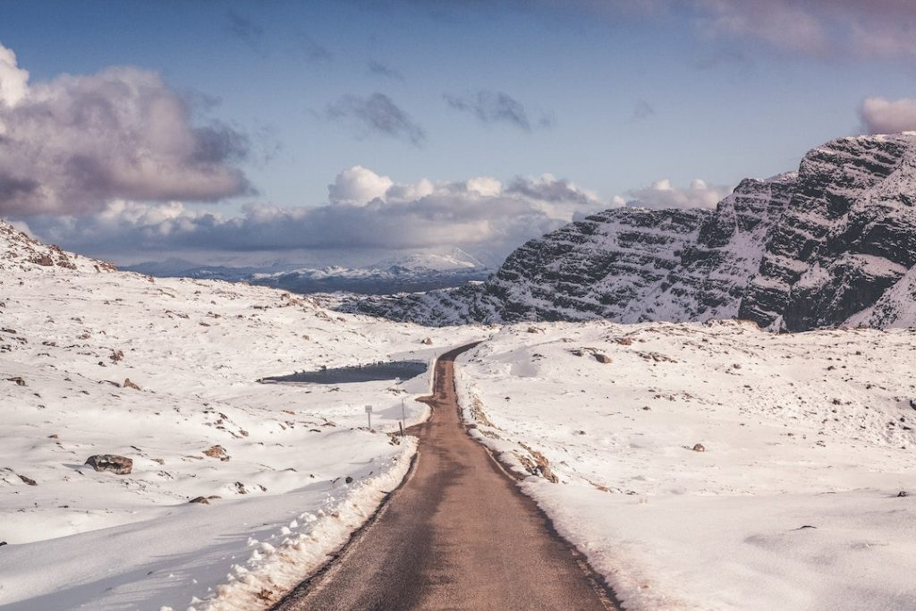 A road among snow-covered valleys in the Scottish Highlands