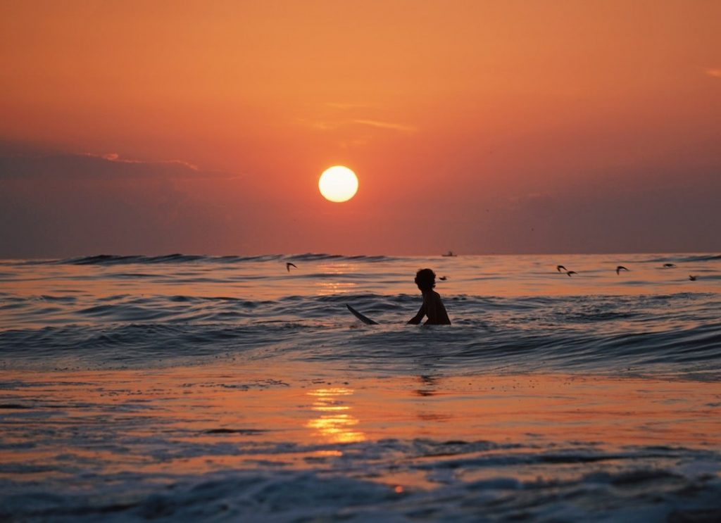 Person floating in the surf at sunset