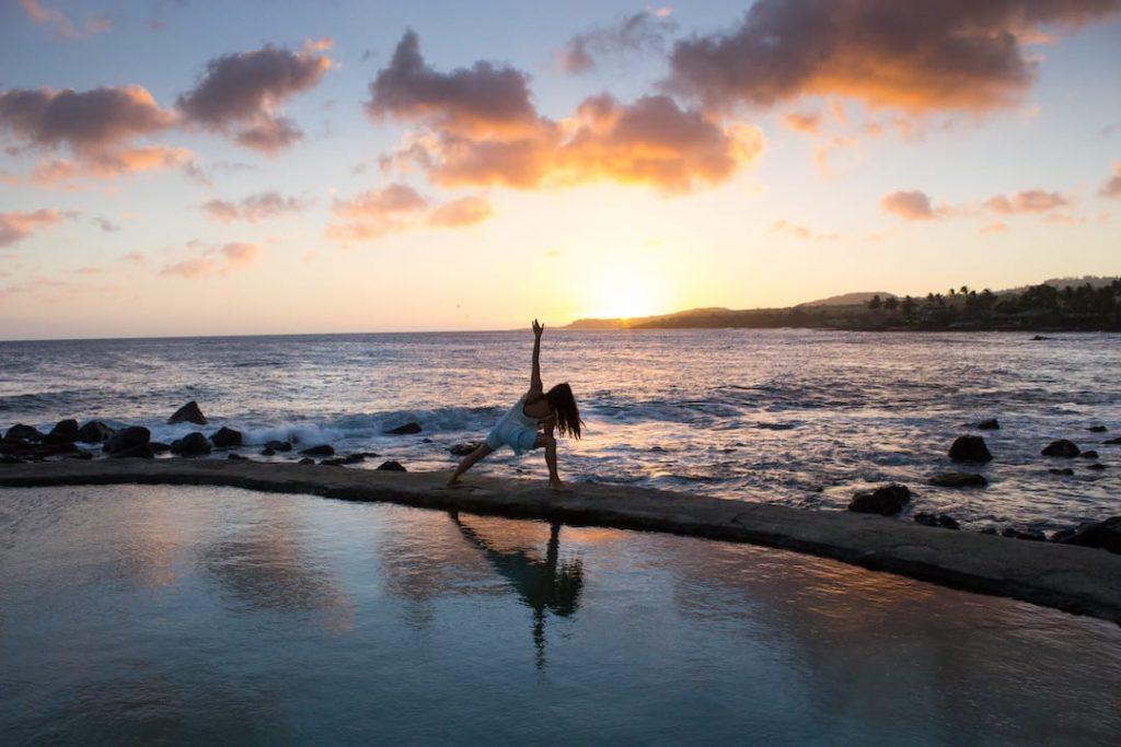 Woman doing yoga on the beach beside the ocean