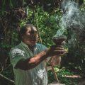man holding brown pot with smoke