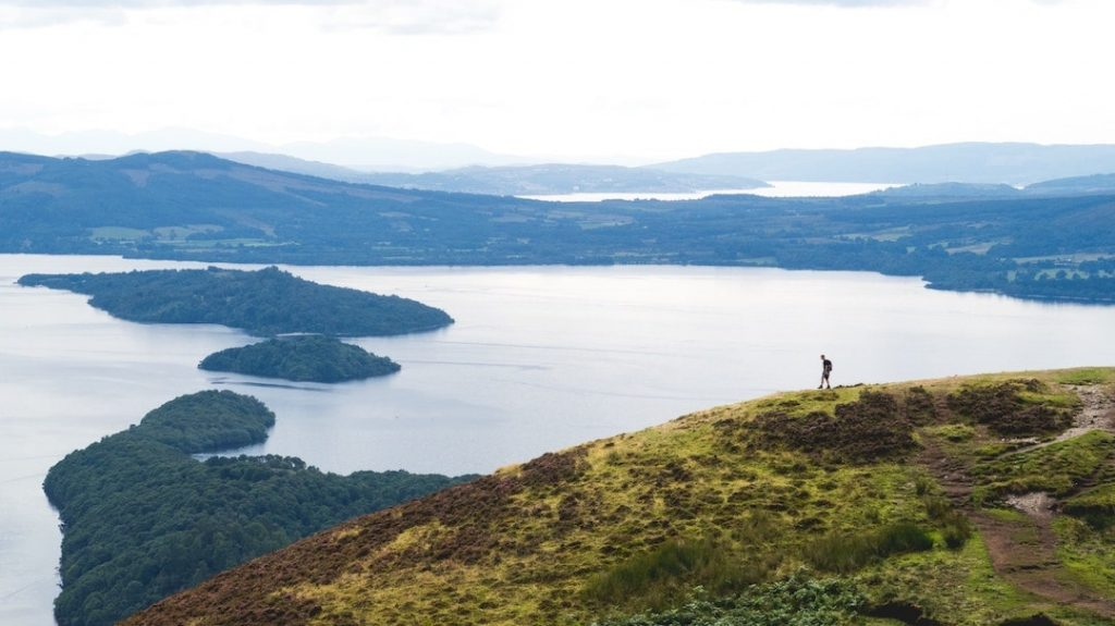 Aerial view of a hiker and Loch Lomond, Scottish Highlands, Scotland
