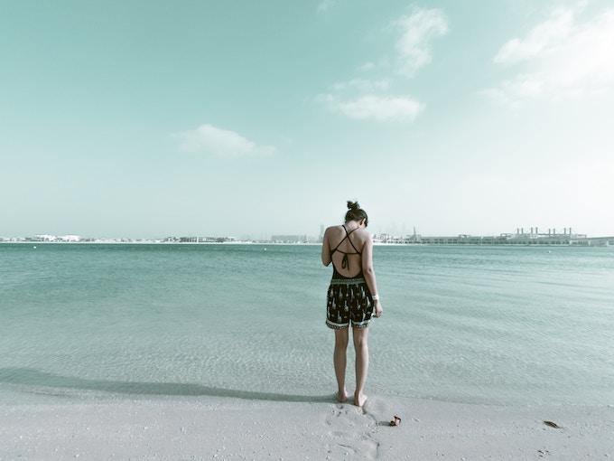 A woman standing on a beach in Dubai, UAE