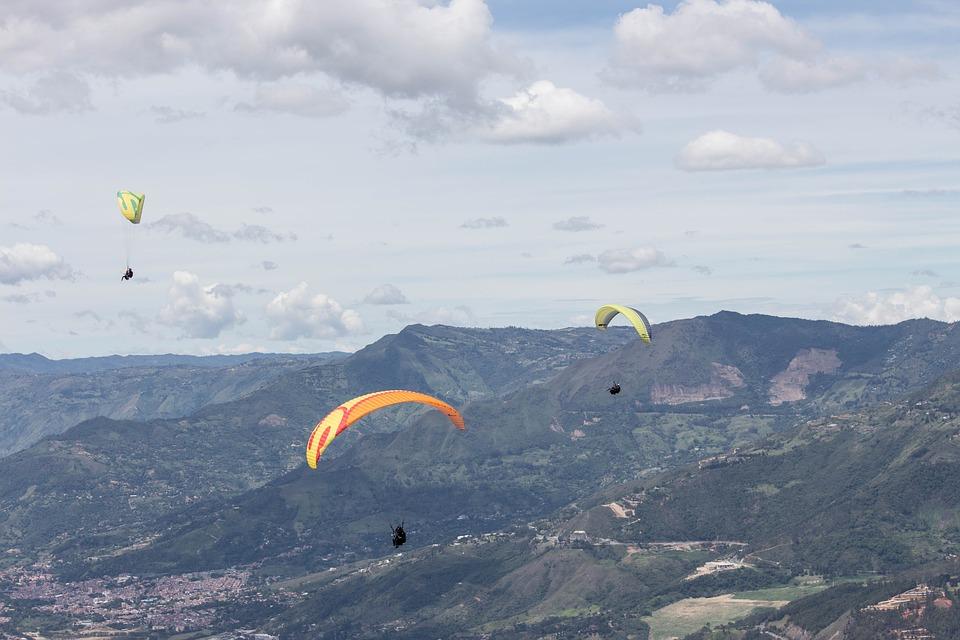 three paragliders soaring through the air across a mountain range