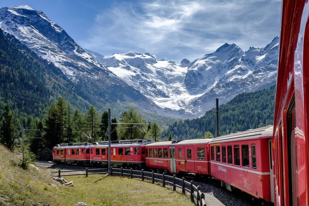 A red train travelling along forest and mountain peaks in Switzerland