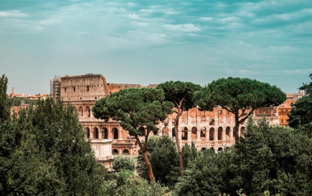 The Colosseum hidden between trees in Rome, Italy