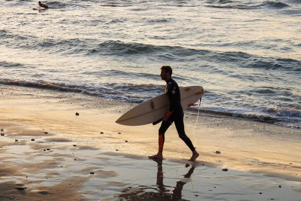 Man holding a surfboarding walking toward the beach in Tel Aviv, Israel