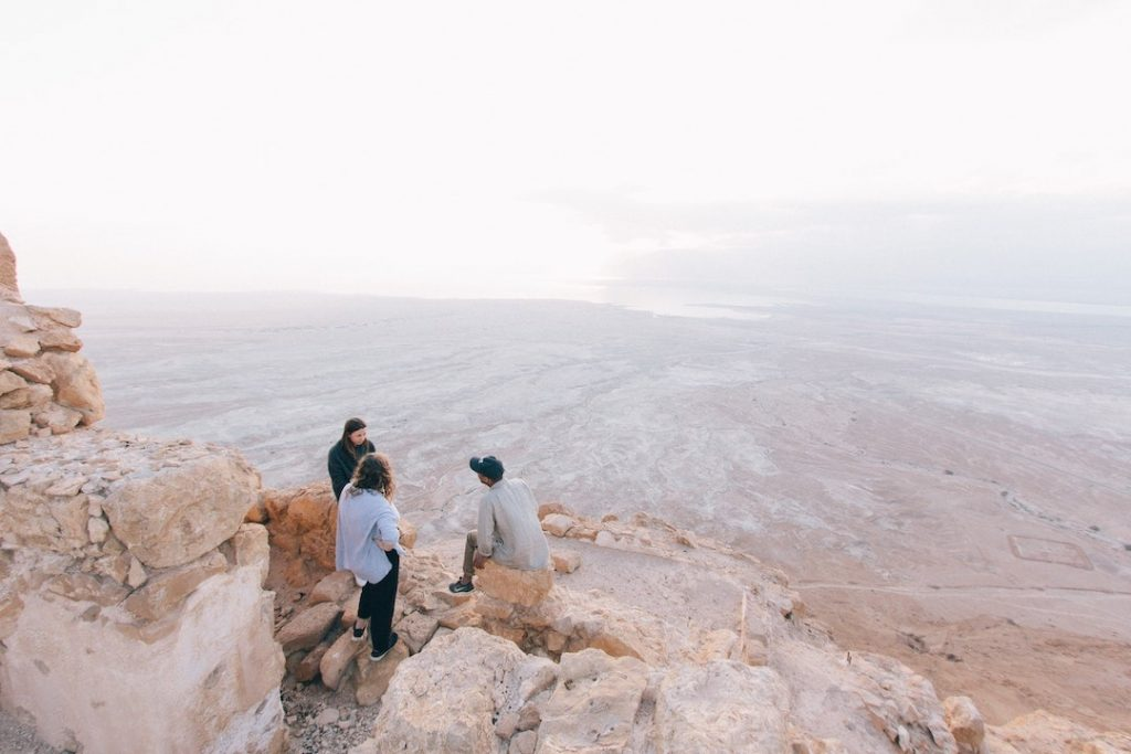 Three people standing on the edge of a cliff in Masada National Park, Israel
