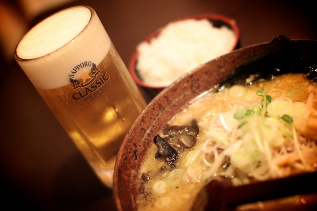 A glass of Sapporo beer and a bowl of ramen in Japan