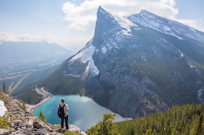 A man standing at the base of a cliff in Alberta, Canada