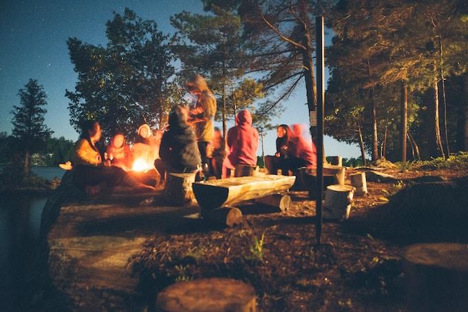 Friends around a campfire in Muskoka, Canada