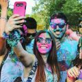 a group of people with colour on their faces taking a picture of themselves