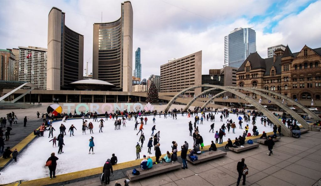 People skating at Nathan Phillips Square in Toronto, Canada