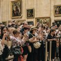 Crowd of tourists trying to take photos of the Mona Lisa in the Louvre in Paris