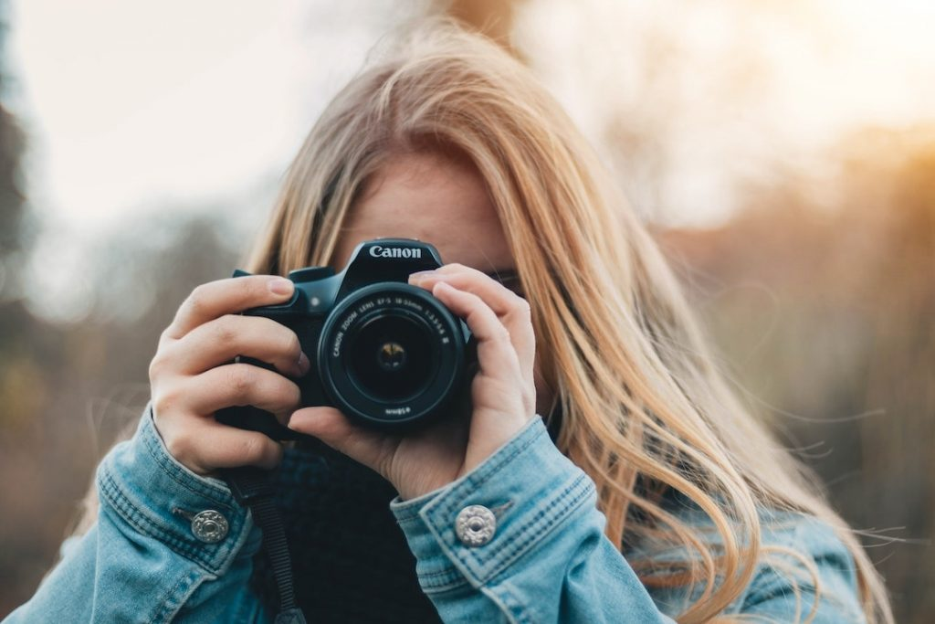 Woman looking through the viewfinder and holding a Canon camera