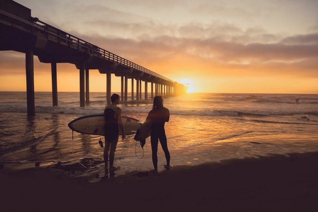 Two people standing on a beach holding surfboards at sunset