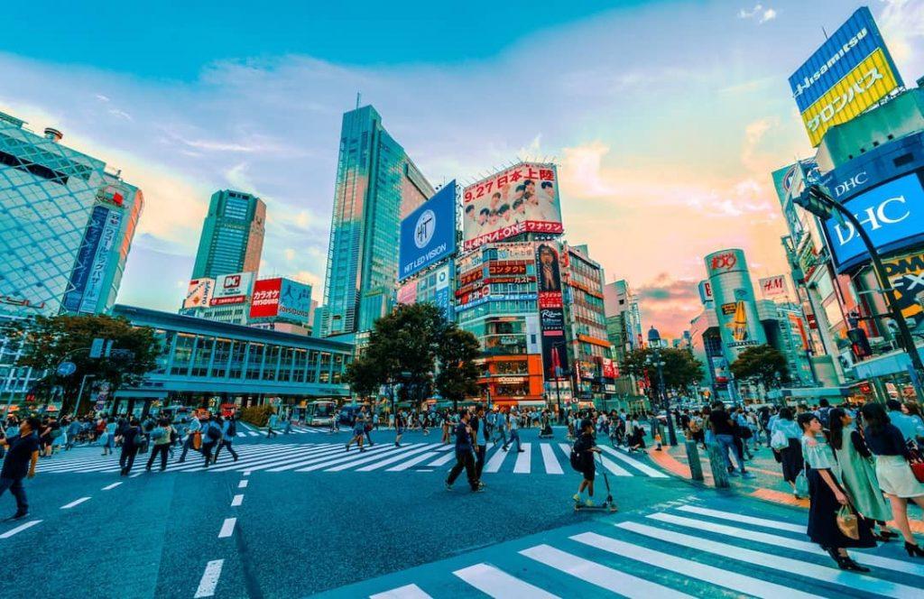 People walking across the street alongside skyscrapers in Tokyo, Japan