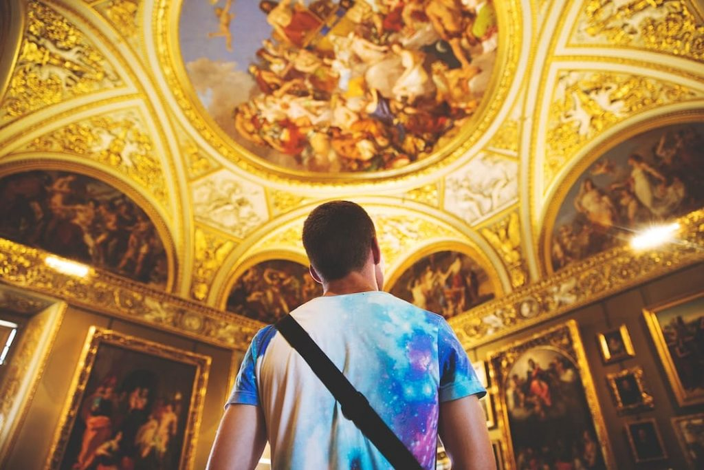 Man looking up at the ceiling in a historic building adorned with frescoes