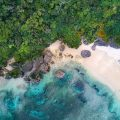 An aerial view of a white-sand beach and forest in Okinawa, Japan