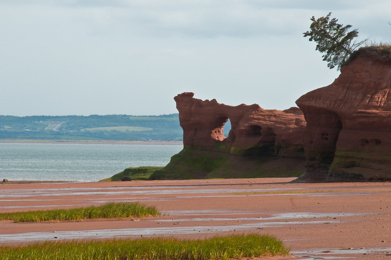 a red ocean bed by the sea with red odd shaped boulders along the coast