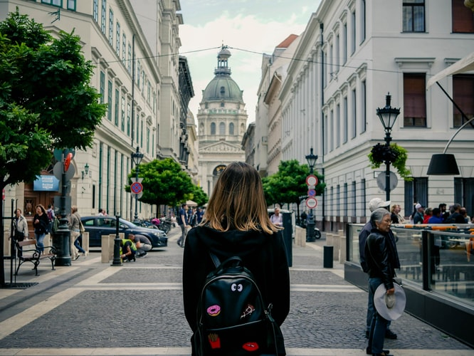 a girl with a backpack standing in the middle of a city