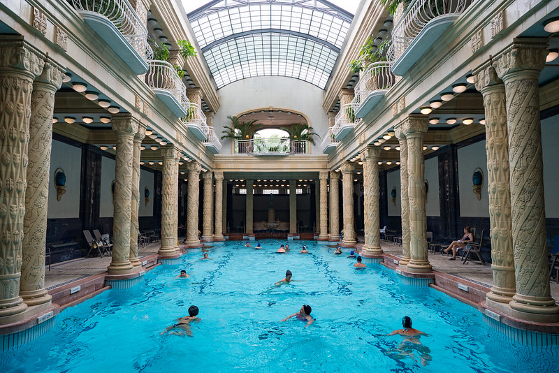 a pool between pillars with people swimming in it