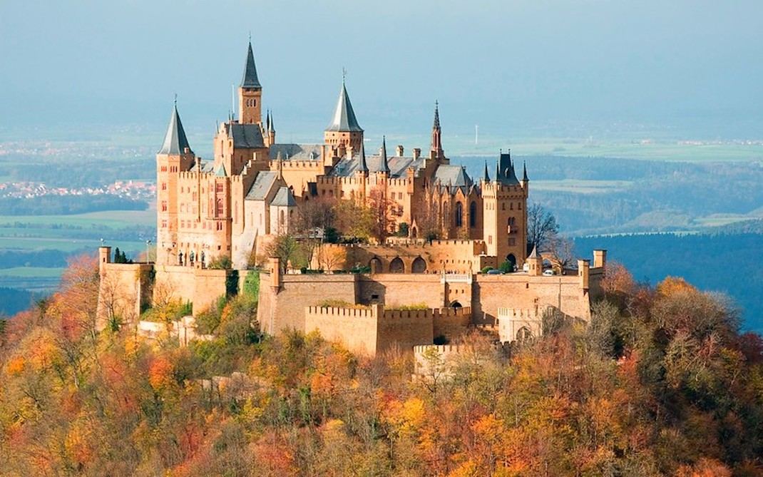 a castle on top of a hillside covered in trees with autumn colours of red, orange and brown