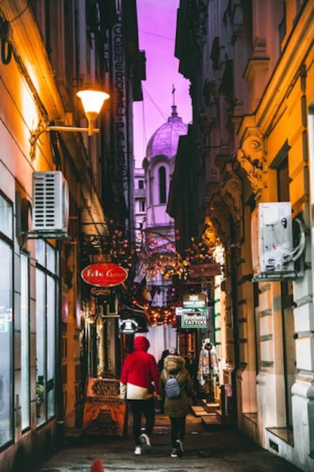 two person walking in a colourful alleyway