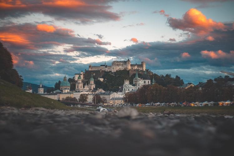 village below castle under cloudy sky during golden hour