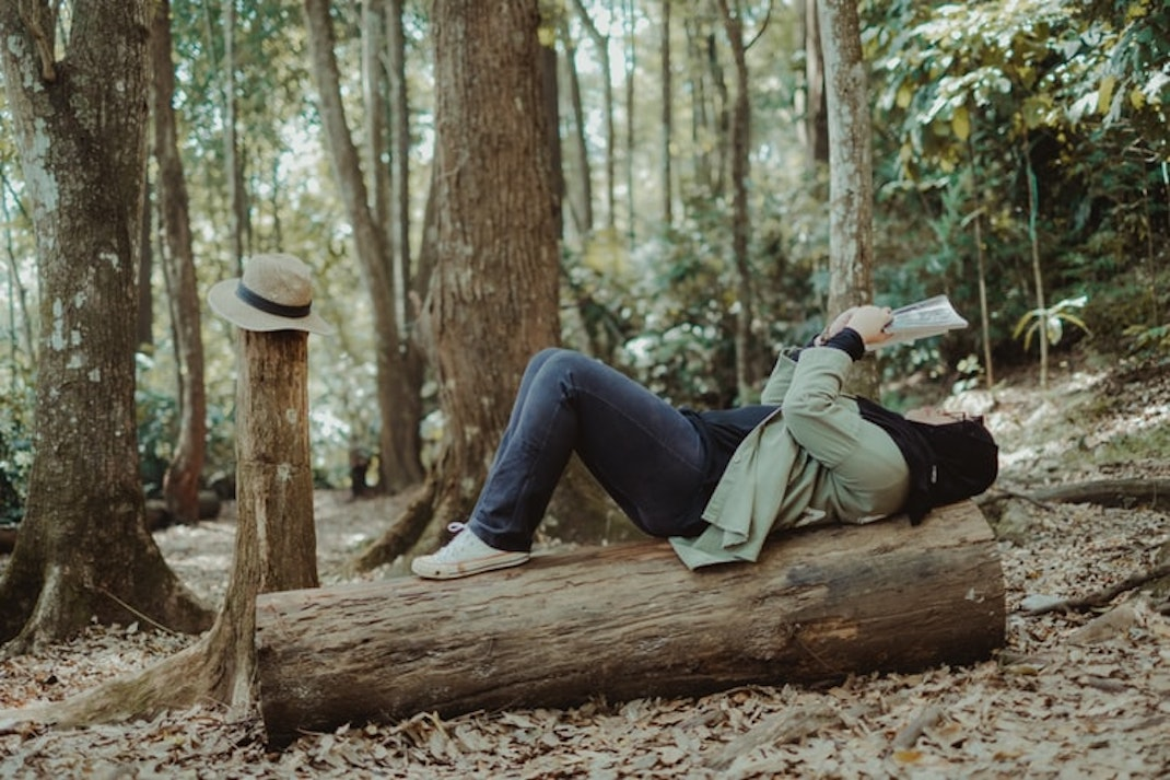 woman lying on a tree trunk reading