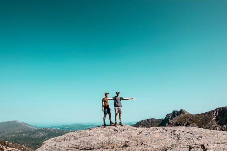 two men standing on top of grey rock hill
