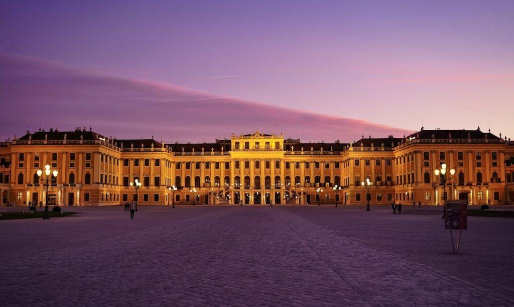 The facade of Schönbrunn Palace against a purple sky at dusk in Vienna, Austria