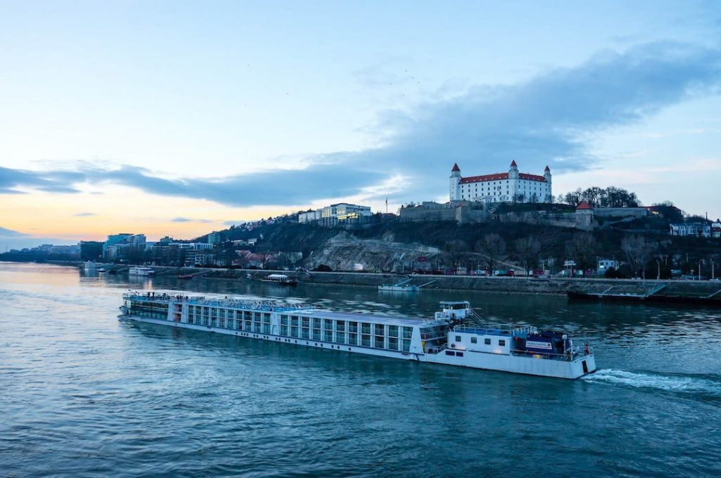 A river cruise ship cruising along the Danube with Bratislava Castle in the background