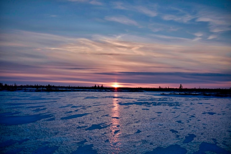 a sunset over an ice landscape