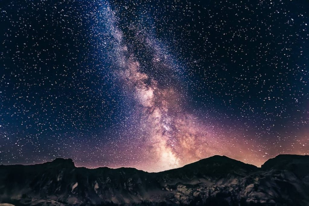 A mountain range with a star-studded sky and the Milky way overhead