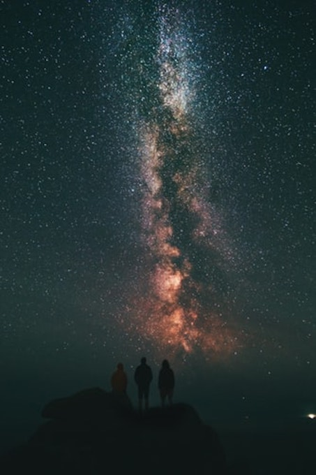 three people looking at the stars and milky way
