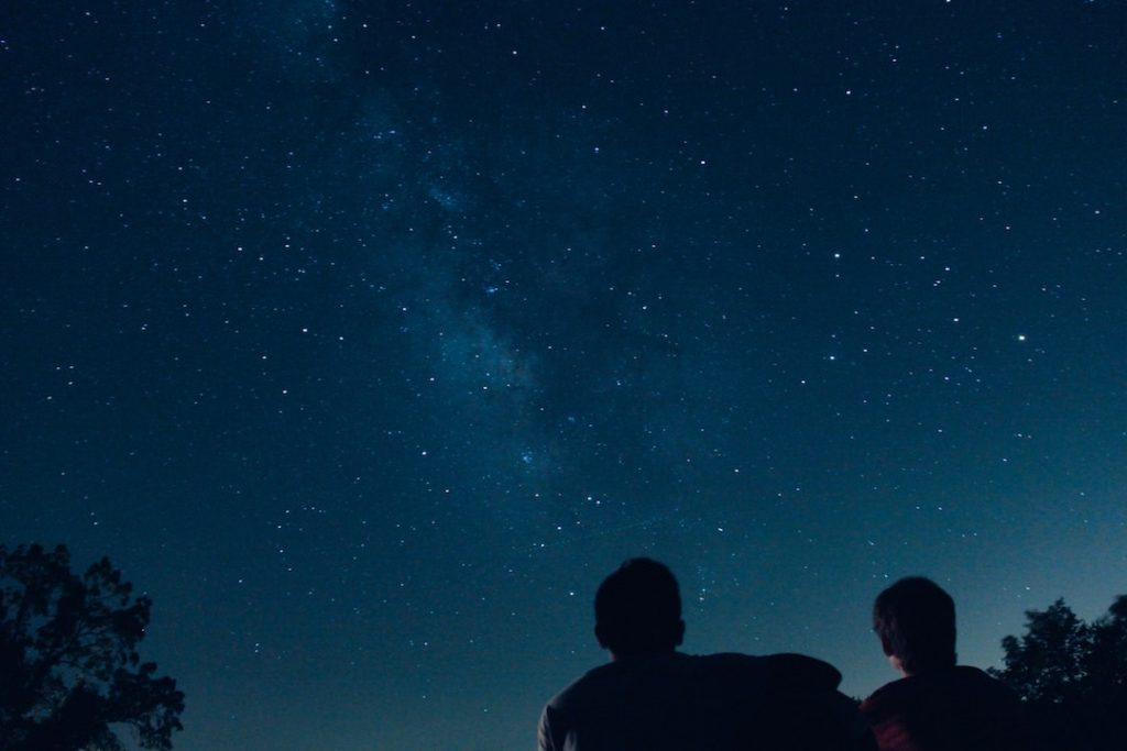 Two people sitting on the ground gazing up at the starry night sky