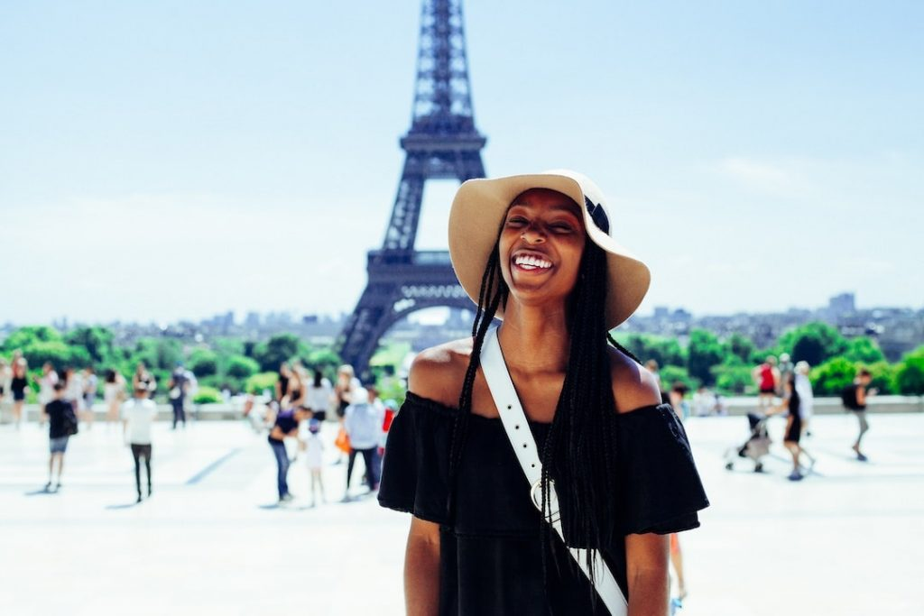 Woman wearing a floppy hat standing in front of the Eiffel Tower in Paris