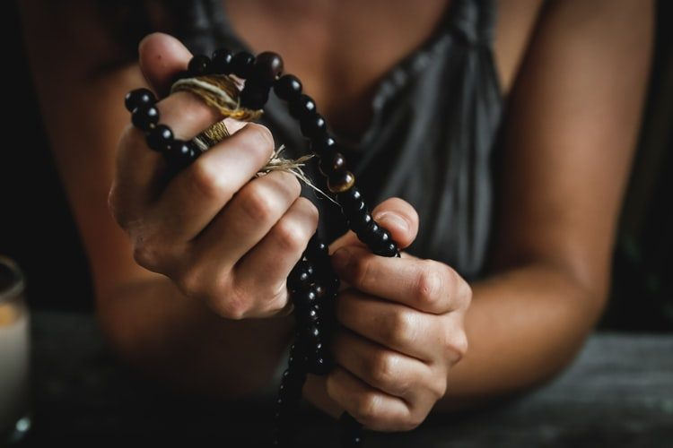 a woman holding prayer beads