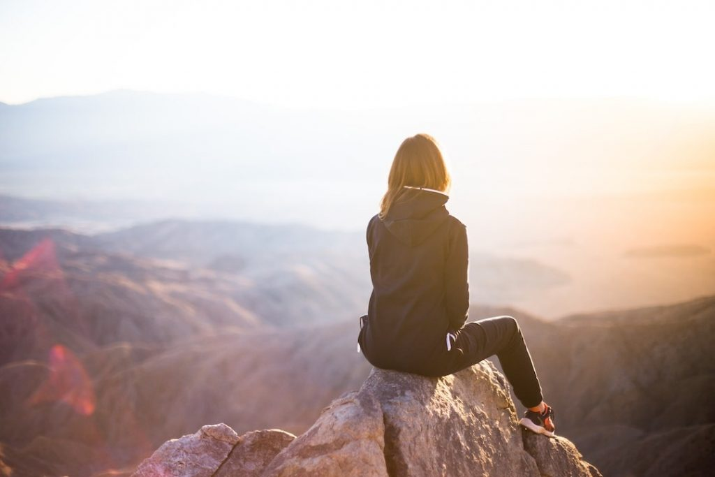 Woman sitting at the top of a mountain overlooking scenic lookout