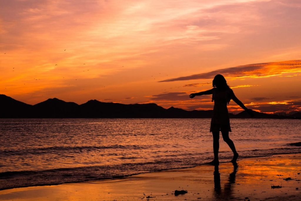 Silhouette of a woman at the shoreline of a beach at sunset