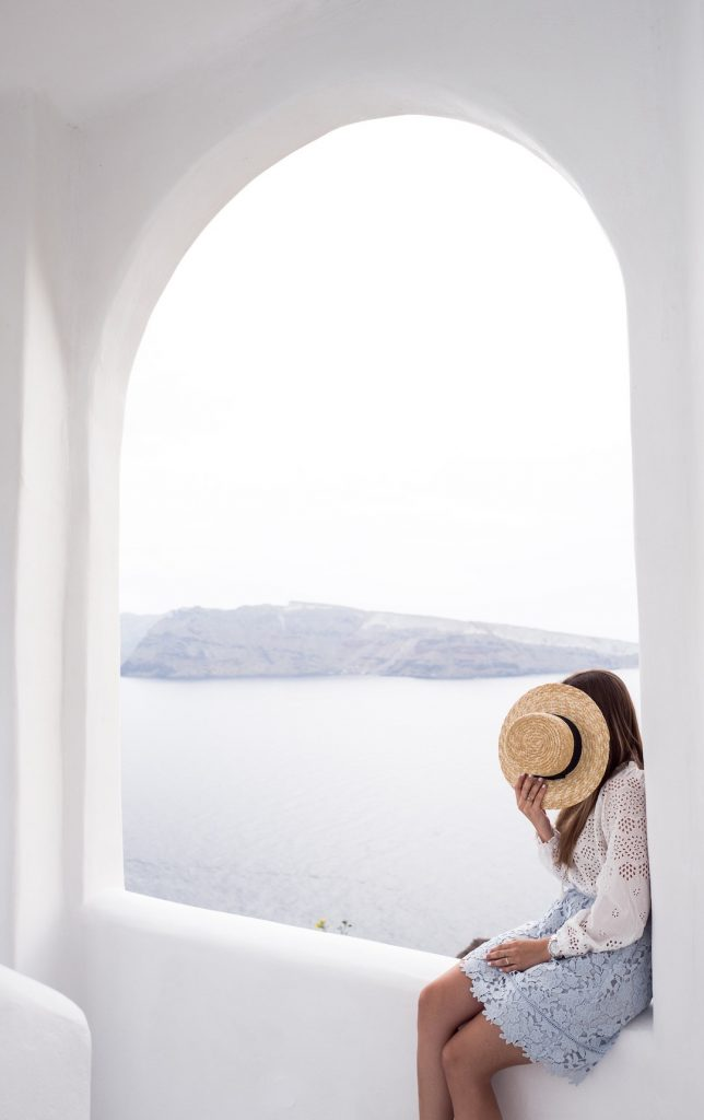 Woman posing with a hat in front of her face with Santorini scenery in the background