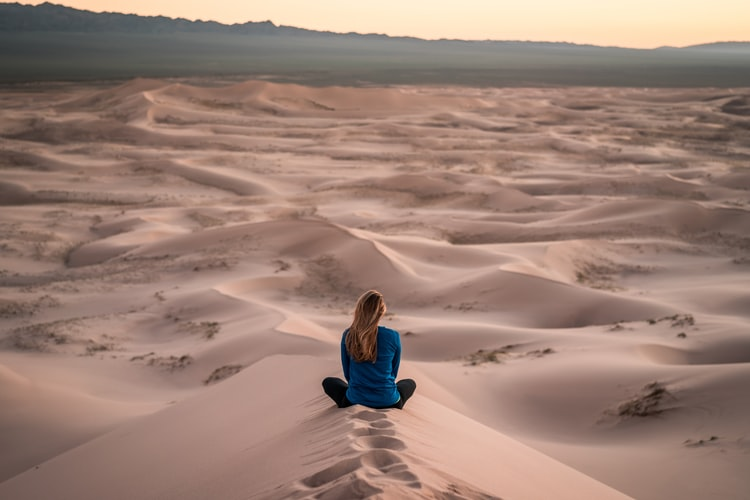 woman sitting crosslegged in the desert looking in the distance