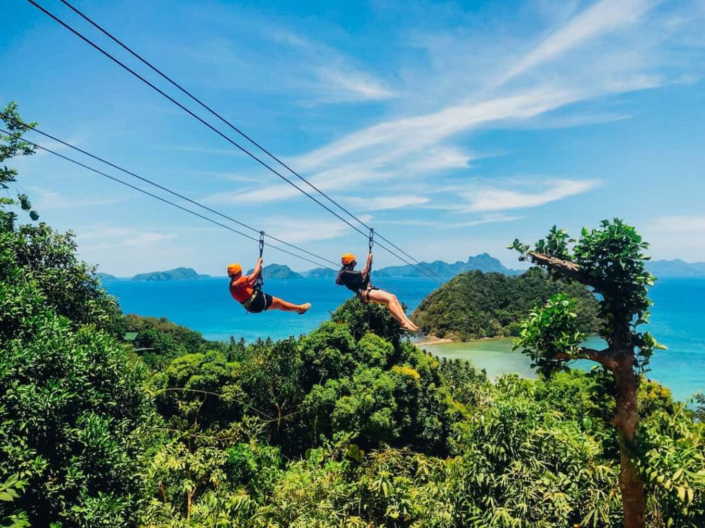 Two people zipling over the beach in the Philippines