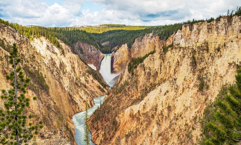 Mountains surrounding a thundering waterfall in Yellowstone National Park