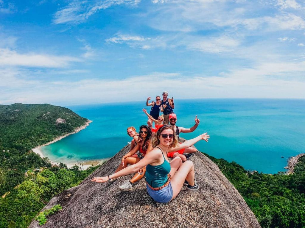 Group of people posing on a lookout point overlooking a beach in Thailand